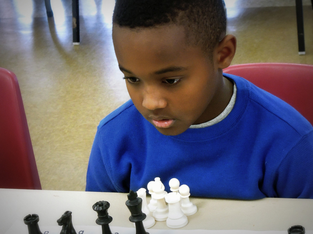 Little kid concentrating on playing chess